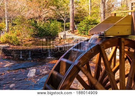 A stream of water falling on the water wheel of the Grist Mill in the Stone Mountain Park Georgia USA