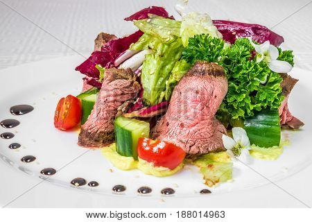 Tasty, Appetizing Pieces Of Sliced Meat With Sauce, Tomatoes, Cucumbers And Herbs, On A White Plate.