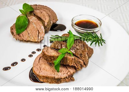 Delicious, Mouth-watering Pieces Of Roasted Meat With Herbs And Sauce, On A White Plate. Horizontal