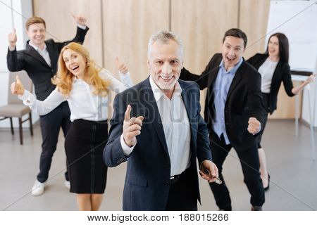 Everything is great. Happy delighted joyful man standing in front of his team and smiling while being in a great mood
