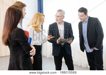 Instructions for the day. Nice serious senior man holding a tablet and speaking with his colleagues while giving them instructions for the day