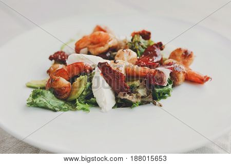 Restaurant food. Traditional italian seafood salad with shrimps and mozzarella on white round plate. Diet and healthy meals closeup