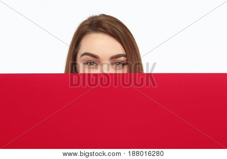 Crop girl looking at camera while standing behind big sheet of red cardboard on white.