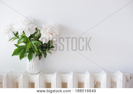 vintage home decoration, fresh peonies in white cozy room interior with empty wall, home decor mockup
