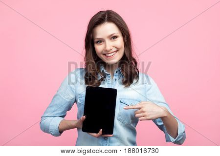 Smiling girl in casual shirt holding and pointing at tablet while looking at camera on pink background.
