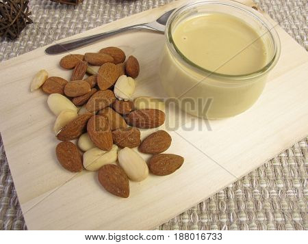 Vegan almond butter in glass and almonds