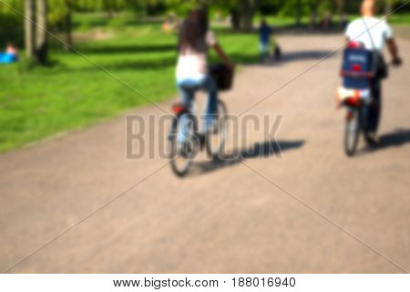 Blurred background texture, people walk and ride bikes in the park