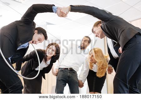 How to be a team. Happy joyful positive people standing in the circle and passing each other a hula hoop while learning how to be a team