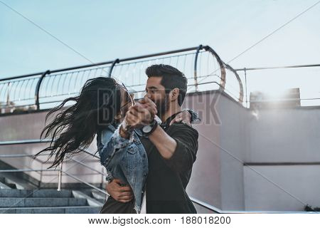 Expressing feelings with a dance. Beautiful young couple dancing and looking at each other while spending time outdoors
