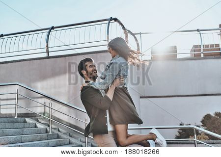 Expressing true love. Handsome man carrying young attractive woman while spending time outdoors