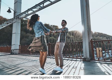 Pure feelings. Full length of beautiful young couple holding hands and spinning while standing on the bridge outdoors