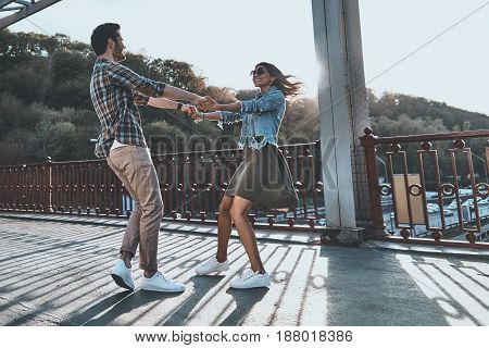 Two hearts full of love. Full length of beautiful young couple holding hands and spinning while standing on the bridge outdoors