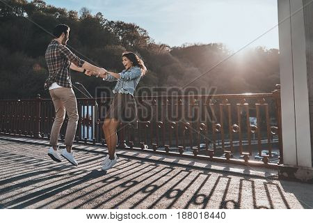 Playful couple. Full length of beautiful young couple holding hands and spinning while standing on the bridge outdoors
