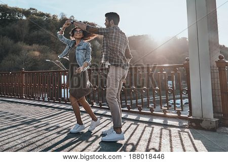 Dancing to the rhythm of love. Full length of beautiful young couple holding hands and spinning while dancing on the bridge outdoors
