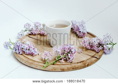 Cup Of Tea With Lilac Spring Flowers On The Wood Table. White Background
