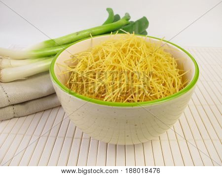 Small soup noodles in bowl and spring onions