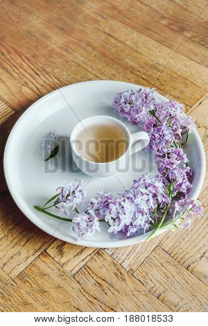 Teacup On The White Plate. Lilac Fresh Flowers.