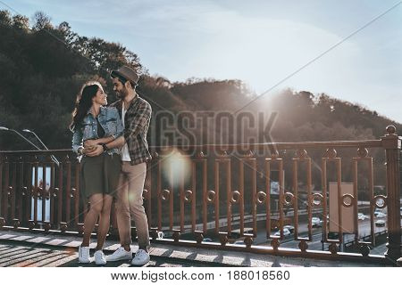 Great date. Full length of beautiful young couple embracing and looking at each other while standing on the bridge outdoors