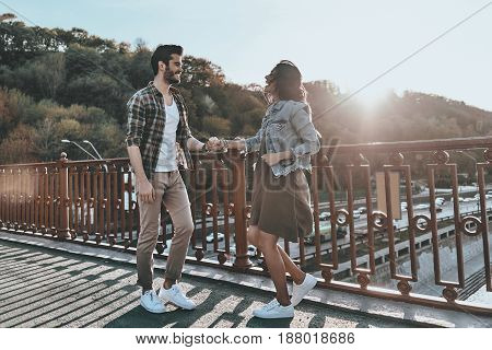 Totally in love. Full length of handsome man looking at young attractive woman and smiling while standing on the bridge outdoors