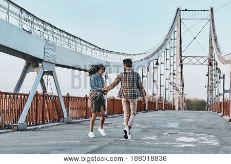 Making each other happy. Full length of playful young couple holding hands while walking on the bridge outdoors