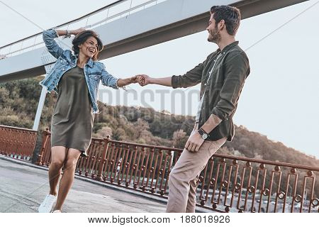 Living this moment. Beautiful young couple holding hands and spinning while dancing on the bridge outdoors