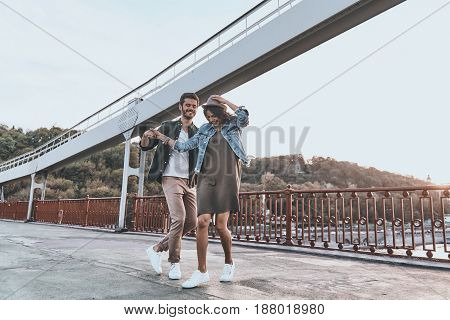 Carefree dance. Full length of playful young couple holding hands and spinning while dancing on the bridge outdoors