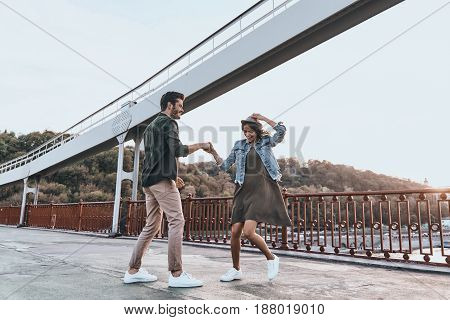 Just dance! Full length of beautiful young couple holding hands and spinning while dancing on the bridge outdoors