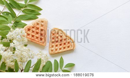 Waffle cookies in the shape of heart on a white background with ashberry branches