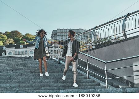 Happy to be together. Full length of handsome man and young attractive woman holding hands while walking down the stairs outdoors