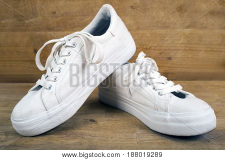 Pair of white sneakers with laces isolated on a wooden background