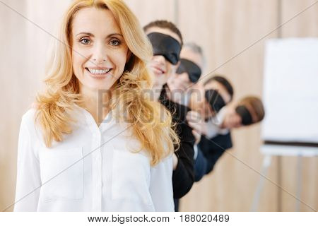 I am the leader. Pleasant nice delighted woman standing in front of her colleagues and leading the team while looking at you