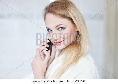 Young Blonde Caucasian woman calling in bathroom