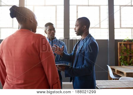 Three focused young African business colleagues deep in discussion while standing together in a bright modern office