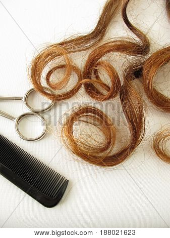 Chestnut brown hair curls, scissors and comb