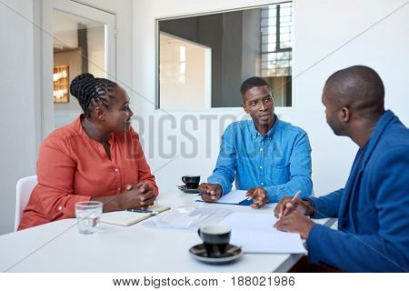Three focused young African businesspeople sitting together at a table in a modern office discussing paperwork