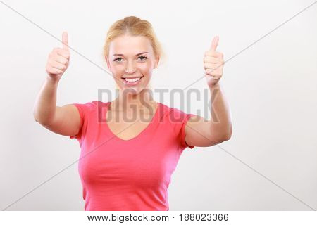 Positive gestures approval and success concept. Happy attractive woman wearing red tshirt showing thumbs up gesture.