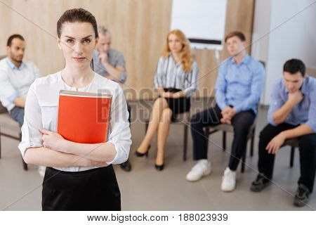 Professional therapist. Serious nice beautiful woman holding her notes and looking at you while being a professional therapist