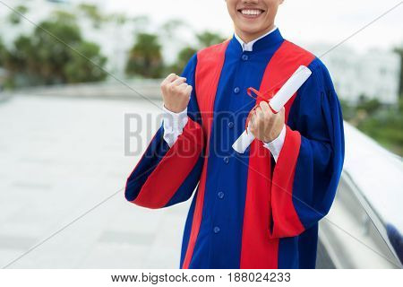Unrecognizable graduate with wide smile doing winner gesture while standing on terrace