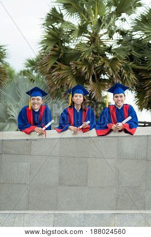 Group portrait of successful graduates holding diplomas in hands and looking at camera with wide smiles, palm trees on background
