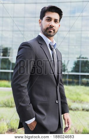 Arabic serious businessman or worker in black suit with tie and shirt with beard standing in front of an office building with hands in pockets on green grass in summer day.