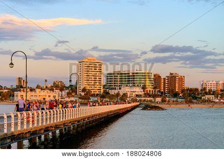 Melbourne Australia - December 28 2016: People walking along St. Kilda Beach jetty at sunset on a hot summer day