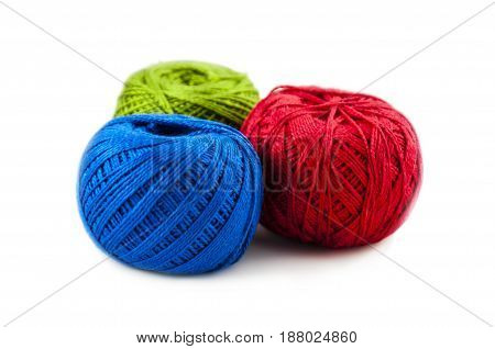 red green and blue color of balls of cotton threads for knitting on a white background
