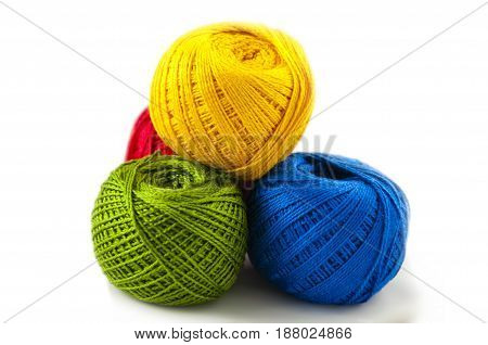 yellow red green and blue color of balls of cotton threads for knitting on a white background