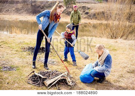 A happy family of four is cleaning outside