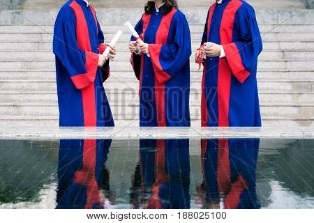 Thee unrecognizable graduates standing in front of university after graduation ceremony and chatting with each other