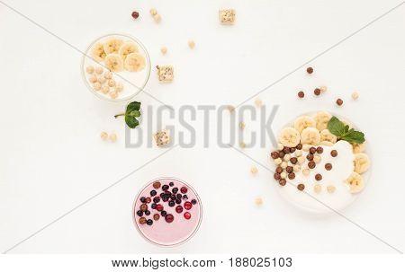 Healthy Breakfast With Yogurt, Muesli, Banana And Berries On White Background. Flat Lay