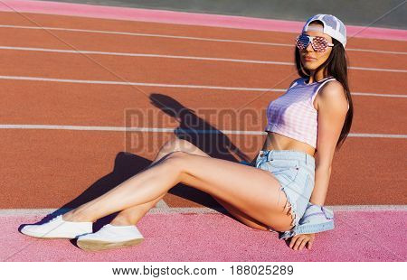 Sport. A fanatical patriot with a leggy beauty posing on the stadium's treadmill in a fashionable summer outfit and the colors of the American flag sunglasses. Fashion.