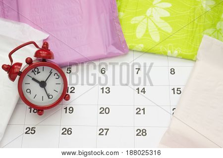 Woman critical days, gynecological menstruation cycle, blood period. Menstrual sanitary soft pads, calendar and a clock. Woman hygiene protection for menstrual period