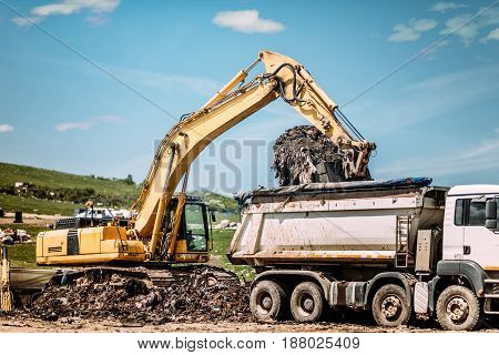 Industrial Excavator Loading Dumper Trucks At Garbage Dumping Site