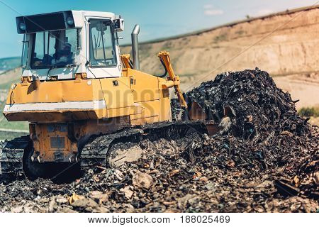 Industrial Bulldozer Pushing Garbage And Working On Trash Site